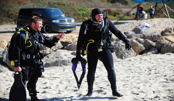 scuba diver geared up on the beach